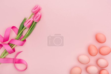 Photo for Top view of pink tulip flowers and traditional easter eggs isolated on pink - Royalty Free Image