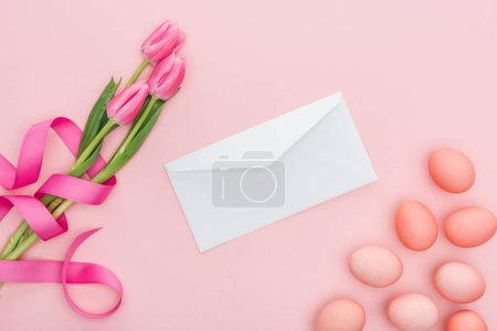 Photo for Top view of greeting envelope, tulips with ribbon and easter eggs isolated on pink - Royalty Free Image
