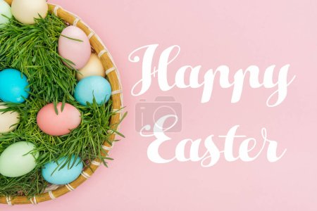 Photo for Top view of painted eggs in wicker plate with grass isolated on pink with Happy easter lettering - Royalty Free Image