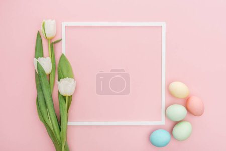 Photo for Top view of frame with tulips and pastel easter eggs isolated on pink - Royalty Free Image