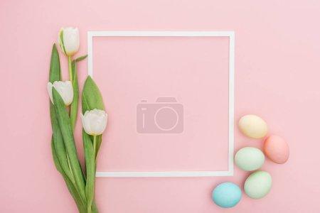 Photo pour Vue de dessus du cadre avec tulipes et œufs de Pâques pastel isolés sur rose - image libre de droit