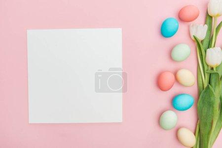 Photo pour Vue du dessus des tulipes et des œufs de Pâques au pastel isolés sur du rose avec planche vide - image libre de droit