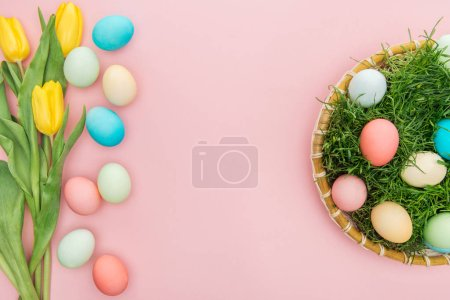 Photo for Top view of tulip flowers and pastel easter eggs in wicker plate isolated on pink - Royalty Free Image
