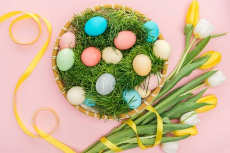 Foto de Vista superior de los huevos de Pascua en placa de mimbre con pastos aislados en rosa con flores de tulipán - Imagen libre de derechos