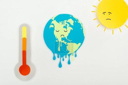 Photo pour Papier coupé soleil et terre fondante avec expression de visages tristes, et thermomètre avec indication de température élevée à l'échelle sur fond gris, concept de réchauffement climatique - image libre de droit