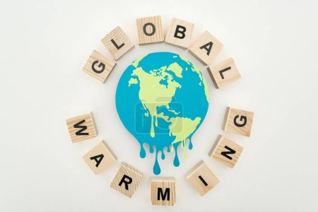 """Photo for Paper cut melting globe surrounded by wooden cubes with """"global warming"""" lettering on grey background - Royalty Free Image"""