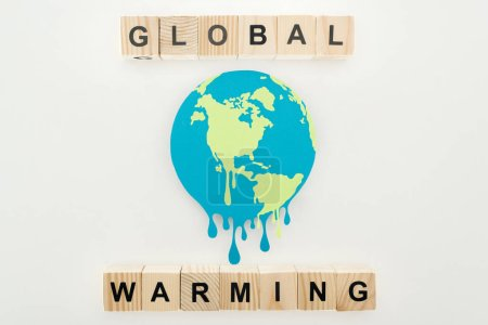 """paper cut melting earth with """"global warming"""" lettering on wooden cubes on grey background"""