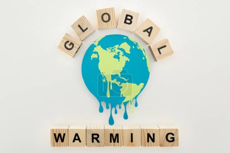 """Photo for Paper cut melting earth and wooden cubes with """"global warming"""" lettering on grey background - Royalty Free Image"""