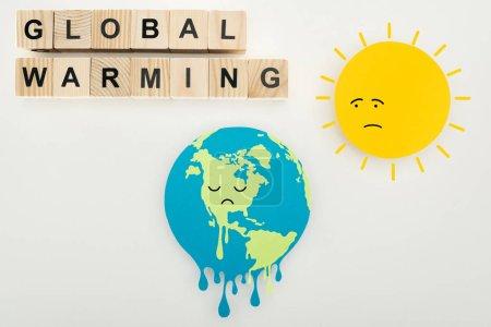 """Foto de Papel corte fusión tierra y sol con expresiones de la cara triste, termómetro con temperatura alta en la escala y el """"calentamiento global"""" rotulación sobre cubos de madera sobre fondo gris - Imagen libre de derechos"""