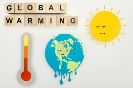 "Photo for Paper cuts melting earth and sun with sad face expressions, thermometer, and wooden cubes with ""global warming"" lettering on grey background - Royalty Free Image"