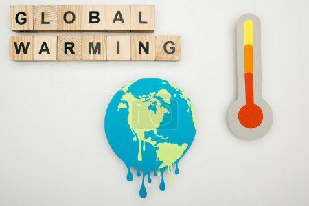 """Foto de Papel corte fusión tierra, cubos de madera con el """"calentamiento global"""" letras y termómetro con indicación de la temperatura del hign en escala sobre fondo gris - Imagen libre de derechos"""