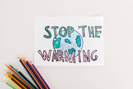 "Photo for Card with earth symbol and ""stop warming"" inscription, and multicolored pencils on white background - Royalty Free Image"