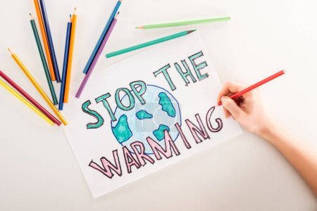"cropped view of woman writing ""stop the warming"" on card with globe sign, and multicolored pencils on white background"