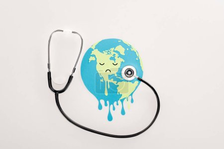 Photo for Paper cut melting globe with sad face expression, and stethoscope on white background, global warming concept - Royalty Free Image
