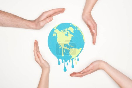 Photo for Paper cut melting earth surrounded by male and female hands on white background, global warming concept - Royalty Free Image