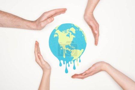Photo pour Papier découpé fusion terre entourée de mains mâles et femelles sur fond blanc, concept de réchauffement global - image libre de droit