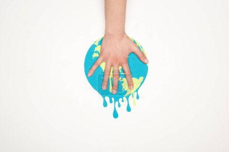 Photo for Cropped view of female hand on paper cut melting globe on white background, global warming concept - Royalty Free Image