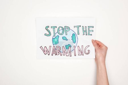 "cropped view of woman holding card with melting globe sign and ""stop the warming"" lettering on white background"