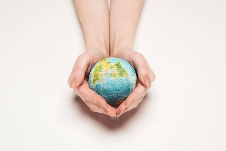 cropped view of woman holding globe model on white background, global warming concept