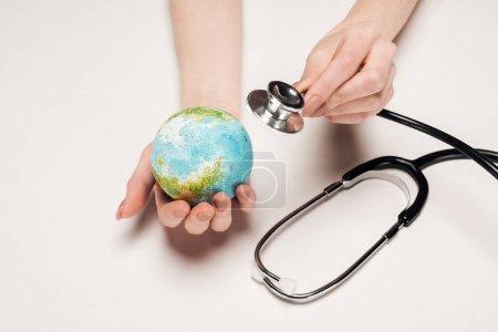 Photo pour Vue recadrée de femme tenant le stéthoscope et globe modèle sur fond blanc, concept de réchauffement global - image libre de droit