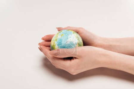 cropped view of female hands with globe model on white background, global warming concept