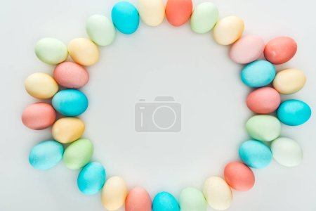 Photo for Top view of pastel easter eggs as circle frame isolated on grey - Royalty Free Image