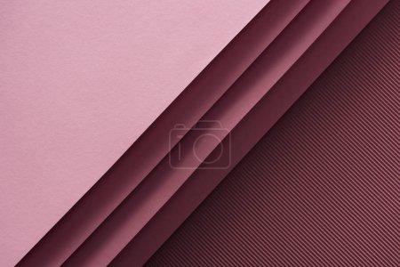 Foto de Vista superior de hojas rosadas y vacías de papel sobre fondo Burdeos - Imagen libre de derechos