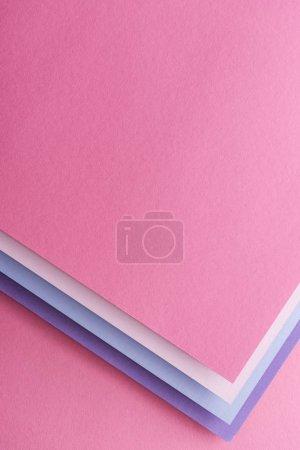 Foto de Vista superior de azules, blancas, rosadas y púrpura hojas de papel en fondo rosa - Imagen libre de derechos