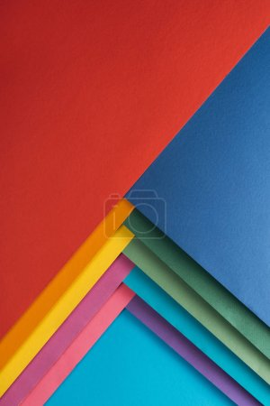 top view of red, blue, orange, burgundy, green, yellow, pink and purple sheets of paper