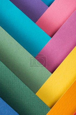 Photo pour Vue de dessus de bleus, orange, Bordeaux, verts, jaunes, roses et pourpres des feuilles de papier - image libre de droit