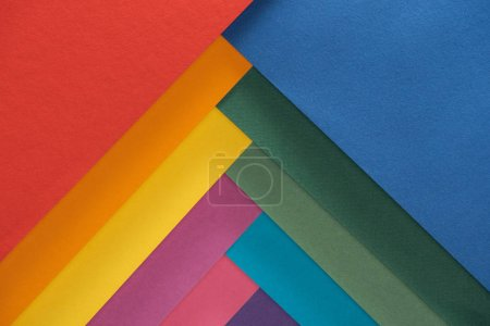 top view of colorful red, burgundy, blue, orange, green, yellow, pink and purple sheets of paper