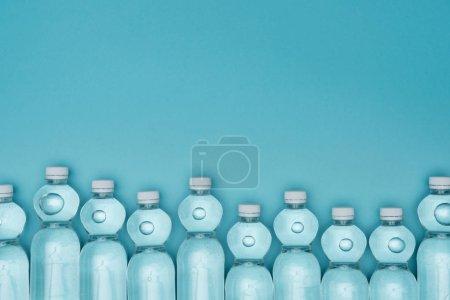 Photo pour Vue de dessus des bouteilles d'eau en plastique isolées sur turquoise avec espace de copie - image libre de droit