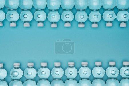 Photo pour Vue de dessus du cadre en bouteilles d'eau en plastique isolées sur turquoise avec espace de copie - image libre de droit