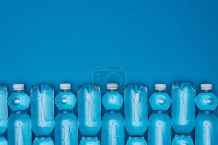 Photo pour Vue de dessus des bouteilles d'eau en plastique disposées isolées sur bleu avec espace de copie - image libre de droit