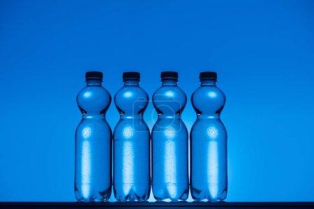 Photo pour Image tonique de bouteilles d'eau en plastique transparent sur fond bleu néon avec rétroéclairage - image libre de droit
