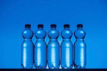 Foto de Tonos de la imagen de botellas de agua sobre fondo azul neón con retroiluminado - Imagen libre de derechos
