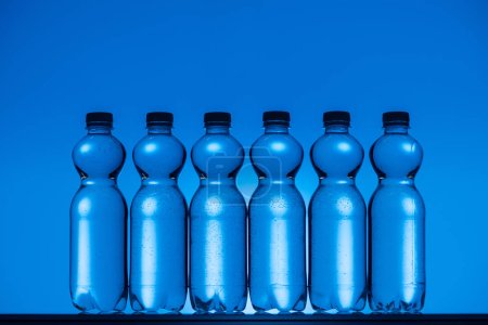 Photo for Toned image of plastic water bottles on neon blue background with back light - Royalty Free Image