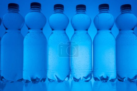 Photo for Toned image of plastic water bottles in row on neon blue background with backlit - Royalty Free Image