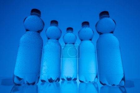 Photo for Toned image of plastic water bottles in row on neon blue background - Royalty Free Image