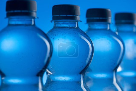 Photo for Close up of transparent plastic water bottles with bubbles in row on blue background - Royalty Free Image