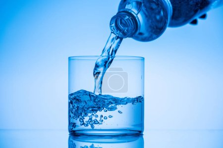 Photo for Cropped view of man pouring water from plastic bottle in glass on blue background - Royalty Free Image