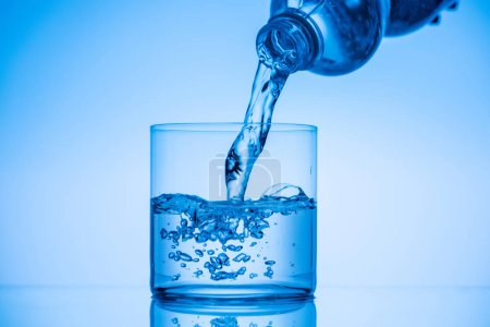 Photo for Water pouring from plastic bottle in drinking glass on blue background - Royalty Free Image