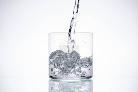 Photo for Water pouring in glass on white background with backlit and copy space - Royalty Free Image