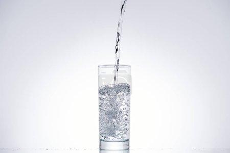 Foto de Agua que vierte en vaso sobre fondo blanco con retroiluminado - Imagen libre de derechos