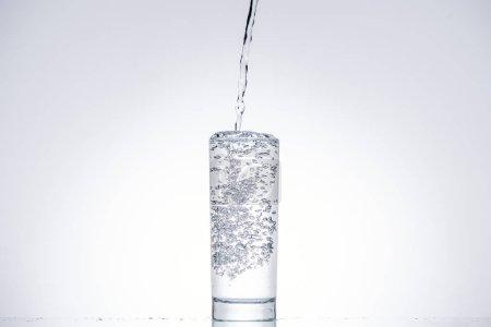 Photo pour Eau, verser dans le verre sur fond blanc rétro-éclairé - image libre de droit