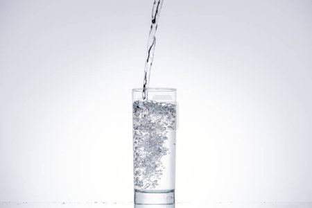 Photo for Background of water pouring in glass on white with backlit and copy space - Royalty Free Image