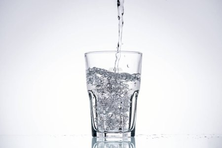 background of water pouring in glass on white with backlit and copy space