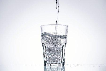 Photo pour Fond de l'eau, verser dans le verre blanc avec l'espace rétro-éclairé et copie - image libre de droit