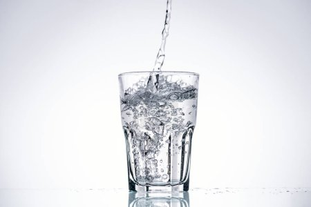 water pouring in drinking glass on white background with backlit and copy space