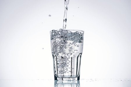 Photo for Water pouring in drinking glass on white background with backlit and copy space - Royalty Free Image
